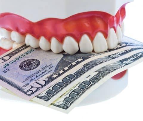 Set of teeth holding dollars