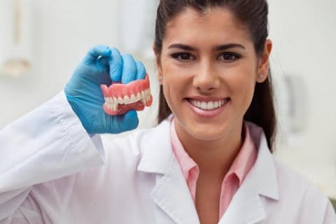 Female dentist holding dentures